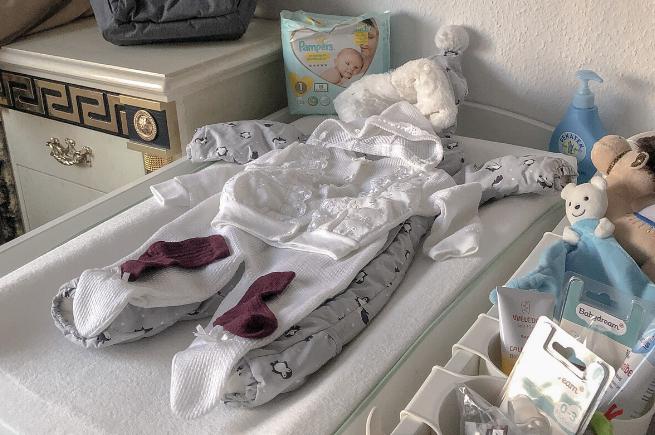 Wickeltisch mit Babyklamotten und Pflege-/ Zubehör